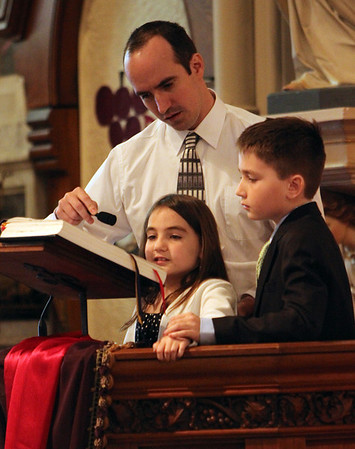 ALLEGRA BOVERMAN/Staff photo. Gloucester Daily Times. Gloucester: Kyler McCaddon, 10, rests his hand on the hand of his sister Madeleine McCaddon, 8, as they read a petition, along with Dan Grund, during the funeral for their father, Capt. Michael Ryan McCaddon, M.D. at St. Ann Church on Tuesday.