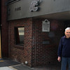 Jack Carter, co-owner of Raymond Alger Gallery on Pleasant Street, stands outside the gallery. The neighboring building has been boarded up and is being worked on a year after a fire caused severe damage, also causing Carter's gallery sufficient water damage. Jesse Poole/Gloucester Daily Times April 12, 2012