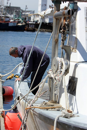 "ALLEGRA BOVERMAN/Staff photographer. Gloucester Daily Times. Gloucester: Ron Riley of Gloucester fixes the rail on his lobster boat, ""My Girls II,"" at the city wharf at the 1-4, C-2 site on Monday morning."