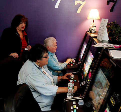 ALLEGRA BOVERMAN/Staff photo. Gloucester Daily Times. Gloucester: Lucky 7 Arcade Manager Janine Brooks, left, helps Carol Sylvain and Joanne White, both of Gloucester, to use the arcade's new machines on Wednesday. Brooks' parents, the owners, have  recently opened another location at the Liberty Tree Mall.