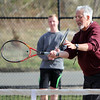 ALLEGRA BOVERMAN/Staff photo. Gloucester Daily Times. Gloucester: Gloucester High School tennis coach Gus Martinson, front right, works with some of the players on the boys tennis team, including Pat Kelley, a junior, behind him, left.