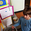 Forth-grader Dakota Geanoulis, representing South Dakota, visits Emily Grace's Nebraska display at the Plum Cove Elementary School state fair event on Thursday afternoon. Jesse Poole/Gloucester Daily Times April 12, 2012