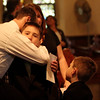 ALLEGRA BOVERMAN/Staff photo. Gloucester Daily Times. Gloucester: Kyler McCaddon, 8, is embraced by Dan Grund during the funeral at St. Ann Church for his father, Capt. Michael Ryan McCaddon, M.D. on Tuesday. Little brother Lucas is at lower right, 6.