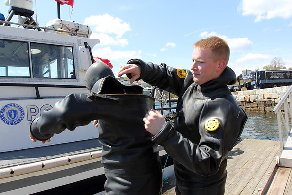 ALLEGRA BOVERMAN/Staff photo. Gloucester Daily Times. Rockport: The search for Caleigh Harrison continues in the Cape Hedge Beach and Long Beach areas of Rockport on Wednesday. State Police marine unit divers Jay Macomber, right and John Strazzullo, left, help each other get suited up before their next dive.