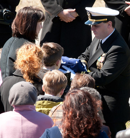 DESI SMITH/Gloucester Daily Times. Gloucester: Leslie McCaddon, left, receives the flag that had lain on her husband's casket from a family friend during the graveside service for her husband, Capt. Michael Ryan McCaddon, M.D., on Tuesday at Calvary Cemetery.