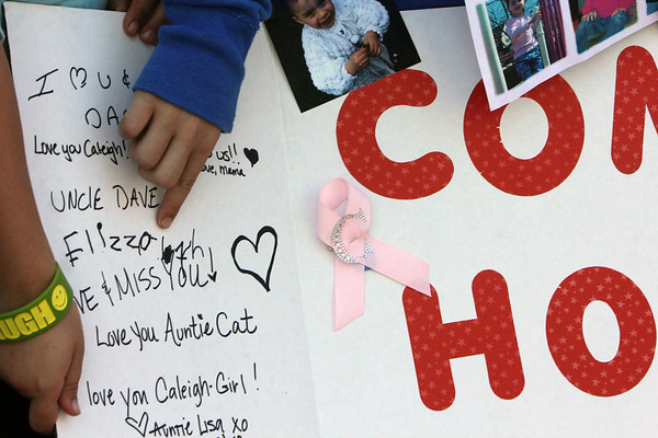 ALLEGRA BOVERMAN/Staff photo. Gloucester Daily Times. Gloucester: Cousins of missing toddler Caleigh Harrison have created a poster in her honor. Showing where Caleigh's sister Lizzy wrote her name on the poster are Angelena Curcuru, 7, and Julia Harrison, 10, both of Gloucester.