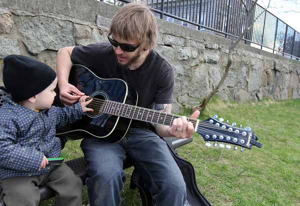 ALLEGRA BOVERMAN/Staff photo. Gloucester Daily Times. Gloucester: Nick Aims plays his guitar with his son Maximus Aims, 1 1/2, occasionally on harmonica, at the Benjamin Smith Playground at Cripple Cove Public Landing on Wednesday afternoon.