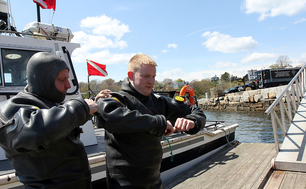 ALLEGRA BOVERMAN/Staff photo. Gloucester Daily Times. Rockport: The search for Caleigh Harrison continues in the Cape Hedge Beach and Long Beach areas of Rockport on Wednesday. State Police marine unit divers Jay Macomber, right, and John Strazzullo, left, help each other get suited up before their next dive.