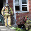 ALLEGRA BOVERMAN/Staff photographer. Gloucester Daily Times. Gloucester: Gloucester firefighters work at the scene of a basement fire at 57 Veterans Way on Monday afternoon.