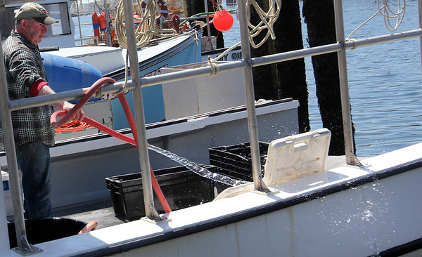 ALLEGRA BOVERMAN/Staff photographer. Gloucester Daily Times. Gloucester: Jim Lane of Gloucester tidies up his lobster boat Mar-Stina in the city wharf at the 1-4, C-2 site on Monday morning.