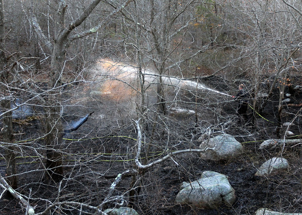 ALLEGRA BOVERMAN/Staff photo. Gloucester Daily Times. Gloucester: Mike Sonia of the Gloucester Fire Department sprays down the earth in Dogtown on Thursday afternoon during the brush fire.
