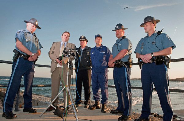 Gloucester: Mass State Police spokesmen speaks to the media at Press conference for a 2-1/2 year old missing girl. Rockport Police Chief Tom McCarthy stands by to answer questions, Thursday afternoon, as a helicopter searches overhead.  Desi Smith/Gloucester Daily Times. April 19,2012