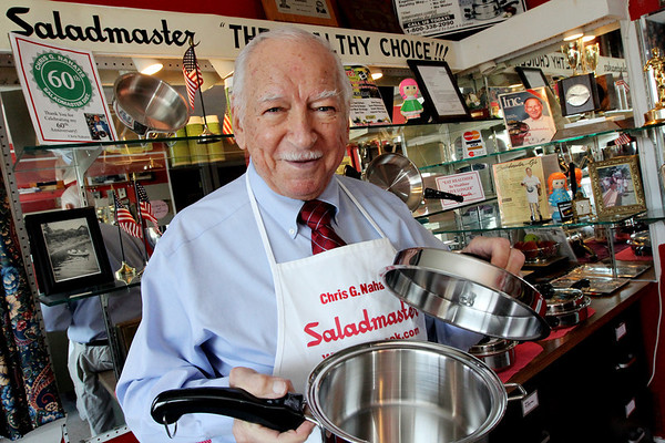 ALLEGRA BOVERMAN/Staff photo. Gloucester Daily Times. Manchester: Chris Nahatis of Manchester is the longtime face and voice of Saladmaster. He is holding one of the company's sauce pans in his shop in Manchester in the home where he grew up.