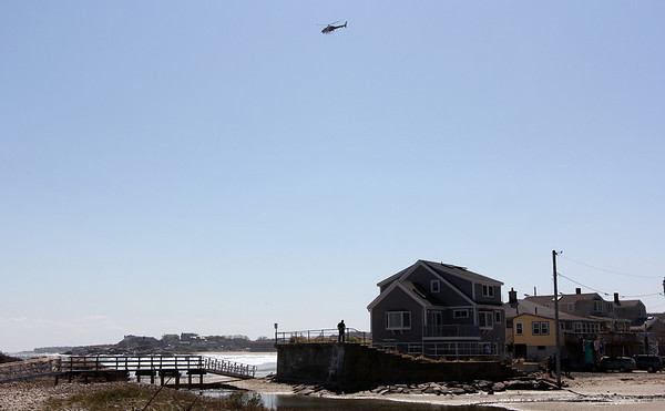 ALLEGRA BOVERMAN/Staff photo. Gloucester Daily Times. Rockport: A Massachusetts State Police helicopter circles around the Long Beach area next to Cape Hedge Beach searching for Caleigh Harrison, 2 1/2, of Gloucester, who went missing in the vicinity of the footbridge and the wall at  right on Thursday.