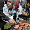 ALLEGRA BOVERMAN/Staff photo. Gloucester Daily Times. Gloucester: About 400 people walked in the 25th Annual Pride Stride through Gloucester on Sunday. At the community cookout following the fundraiser walk at Stage Fort Park, Rotary Club of Gloucester members Joe Ciolino, left, and Bill Cox cook hamburgers and hotdogs as fast as they can.