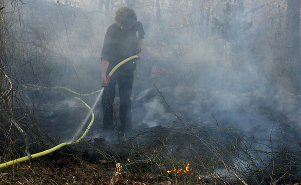 ALLEGRA BOVERMAN/Staff photo. Gloucester Daily Times. Gloucester: Paul Serrin of the Gloucester Fire Department sprays down parts of the brushfire in Dogtown on Thursday afternoon.