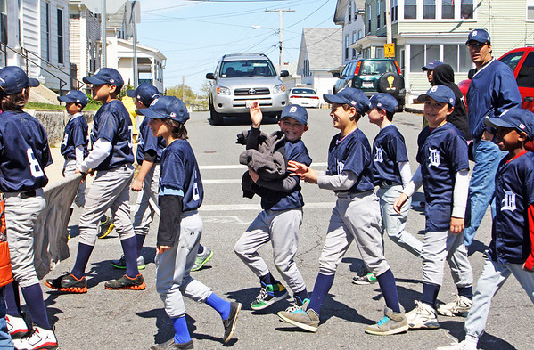 A player on the Tigers team waves to the crowd gathered to watch the Gloucester Little League Parade march down Prospect Street on Saturday morning. Jesse Poole/Gloucester Daily Times April 28, 2012