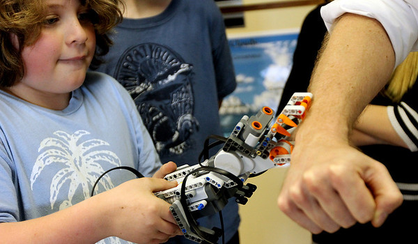 ALLEGRA BOVERMAN/Staff photo. Gloucester Daily Times. Rockport: John Paul Penaloza, left, playfully has the robot he and friends Thomas Micalizzi and Michael Newman are working on bite Robotics Club leader Eric Wilson <br /> during the Robotics Club meeting on Monday afternoon at the school. The club is new to the school this academic year and runs for 6-7 weeks at a time. It is run by volunteer and engineer Wilson who works at Varian in Gloucester. Varian donated several laptops and matched donations to the club.