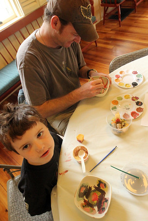 ALLEGRA BOVERMAN/Staff photo. Gloucester Daily Times. Rockport:<br /> Keith Hickey, of Byfield, top, and his son Sam Pallazolla, 5, of Gloucester, <br /> paint bowls on Wednesday at Rockport Council on Aging at Community House for the upcoming Open Door Empty Bowl Dinner on Thurs., May 10 from 4-8 p.m. at Cruiseport Gloucester. They also enjoyed Hoodsies ice cream cups while there.