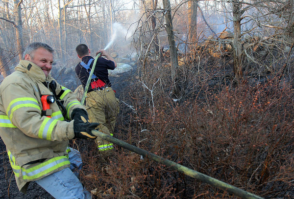ALLEGRA BOVERMAN/Staff photo. Gloucester Daily Times. Gloucester: Jay Prince, front left, helps pull more hose for Rob Gerety of the Gloucester Fire Department as he attacks a piece of the leading edge of the brushfire in Dogtown on Thursday afternoon.