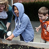 ALLEGRA BOVERMAN/Staff photo. Gloucester Daily Times. Gloucester: First graders at Veterans Memorial Elementary School were planting yellow beet seeds, dissecting and studying beans and seeds on Friday afternoon at the school. From left are FoodCorps service member serving with CitySprouts, Sarah Rubin, pouring cool water over the hands of first grader Kayky Barbosa to both clean his hands and add water to the seeds he planted, and Nicholas Carvino.