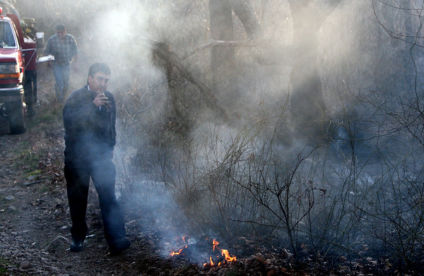 ALLEGRA BOVERMAN/Staff photo. Gloucester Daily Times. Gloucester: Gloucester Deputy Chief Joe Aiello walks by a section of the burning brushfire in Dogtown on Thursday afternoon.