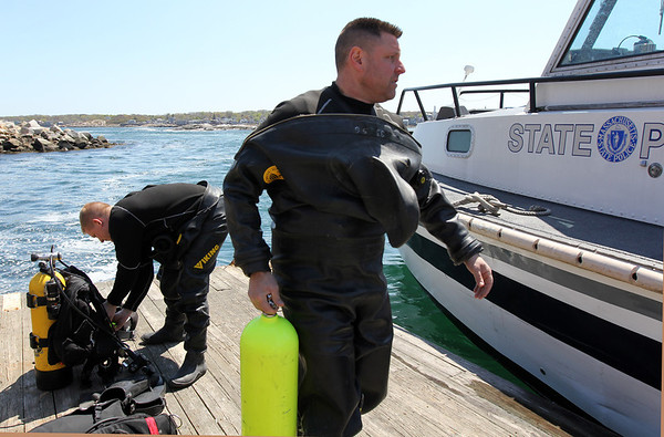 ALLEGRA BOVERMAN/Staff photo. Gloucester Daily Times. Rockport: The search for Caleigh Harrison continues in the Cape Hedge Beach and Long Beach areas of Rockport on Wednesday. State Police marine unit divers Jay Macomber, far left, and John Strazzullo, right, get suited up and preparing their compressed air tanks for their next dive.