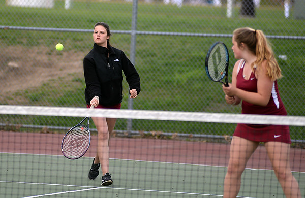 RYAN HUTTON/ Staff photo<br /> Gloucester's Heidi Franke-Otten, left, runs to intercept the ball as her partner Katie Nugent, right, looks on during their 1st Doubles match against Peabody's Chrisly Biqiku and Andeemae Sims during Monday's tennis match at Peabody High.