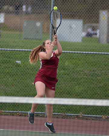 RYAN HUTTON/ Staff photo<br /> Gloucester's Katie Nugent leaps to hit the ball during her 1st Doubles match with partner Heidi Franke-Otten against Peabody's Chrisly Biqiku and Andeemae Sims during Monday's tennis match at Peabody High.