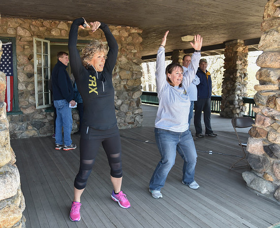 Desi Smith/Staff photo.    Fitness instructor Martha Rumble (left) of the Fitness Zone in Gloucester, along with City Countselor Melissa Cox, leads a crowd of walker through a warm up exercise before the start of the 29th Annual Pride Stride Walk that started and ended at Stage Fort Park Sunday afternoon,even a group of firefighters from Rockport in full gear.   April 24,2016