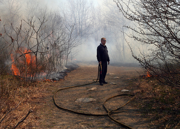 Gloucester: Gloucester Firefighter Mike Sonia waits for more water while battling a brush fire on Poles Hill yesterday afternoon. Photo by Kate Glass/Gloucester Daily Times