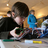 Jack Rukeyser, a student at Rockport Middle School, works on the electronic components of his remote operated vehicle at the Gloucester Maritime Heritage Center during a school vacation program. Photo by Kate Glass/Gloucester Daily Times