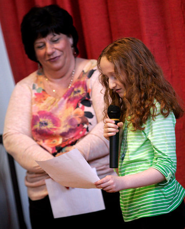 Gloucester: Plum Cove Elementary School Principal Tammy Morgan listens as 5th grader Brianna Biondo reads a letter the school received after sending valentines to troops overseas. Four members of the military wrote back to the students and their letters were read aloud during an assembly on Friday. Photo by Kate Glass/Gloucester Daily Times