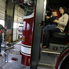 Gloucester: Natalie Berthiaume holds her son, Luke, almost 2, so he can pretend to steer Ladder 1 as her husband, Jason, holds their two-month-old daughter, Maggie, who was delivered by Gloucester paramedics in January. Photo by Kate Glass/Gloucester Daily Times