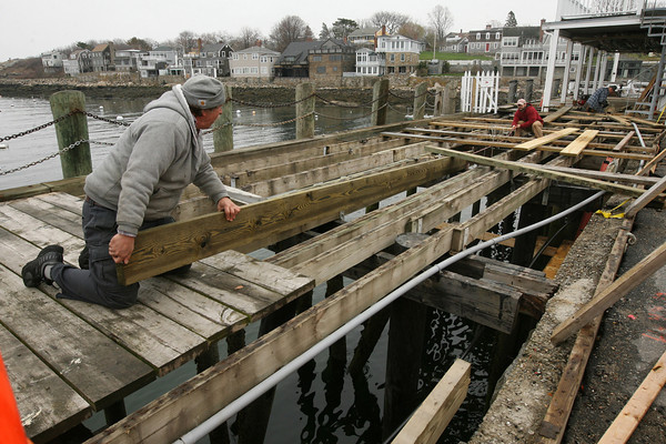 Rockport: Christopher Krenn and James Greenan help rebuild the base for the dock at the end of T Wharf. The dock was damaged during a storm in December. Photo by Kate Glass/Gloucester Daily Times