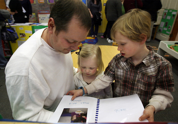 "Gloucester: Hugh Cauthers and his son, Deston, read Georgana Cauthers' book, ""A Book About Me,"" during an open house at the Gloucester Preschool in the Fuller School on Wednesday night. The students got to share some of their favorite activities from school with their families. Photo by Kate Glass/Gloucester Daily Times"