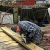 Rockport: Jack Munro trims a board while making repairs to the dock at the end of T Wharf. The dock was damaged during a storm in December. Munro has made repairs to the dock four other times due to storms and says it is designed to break with the water pressure to minimize overall damage. Photo by Kate Glass/Gloucester Daily Times