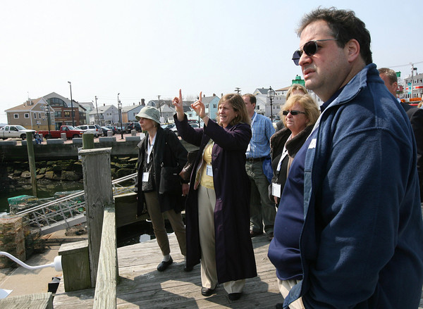 "Gloucester: Sara Buck Garcia, Gloucester's Community Development Director, points out several fishing trawlers in Gloucester Harbor while leading a tour of the waterfront to attendees of the American Planning Association's National Planning Conference yesterday. The group toured the Gloucester waterfront as part of a ""Sustaining and Strengthening the Working Waterfront"" mobile workshop. Photo by Kate Glass/Gloucester Daily Times"