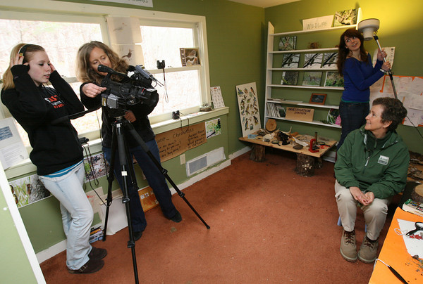 Gloucester: Lisa Smith of Cape Ann TV shows Samantha Delaney-Burke how to frame a shot as Patrice Kelly holds the light while interviewing Ramona Latham of the Trustees of Reservations in the Cape Ann Discovery Center at Ravenswood Park. The students have been participating in an after school video program and focused on their Earth Day Special program over April vacation. Photo by Kate Glass/Gloucester Daily Times