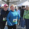 Gloucester: Runner Abby Berry of Chelmsford congratulates her friend Rose Mitrano of Burlington,Mass, as they heads to the finish. This was Rose's 1st race. Desi Smith/Gloucester Daily Times.April 9,2011.