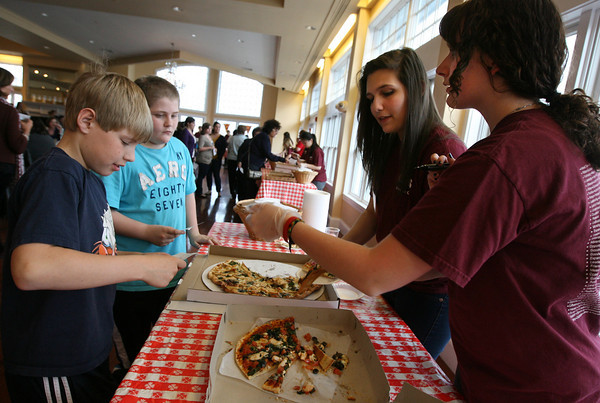 Gloucester: Leneai Stuart, right, and Michaela Kotob of the Gloucester High School Interact Club hand pizza to Nick Blake, left, and Matthew Wayrynen during the 4th Annual Pizza Taste-Off at Cruiseport yesterday evening. Photo by Kate Glass/Gloucester Daily Times