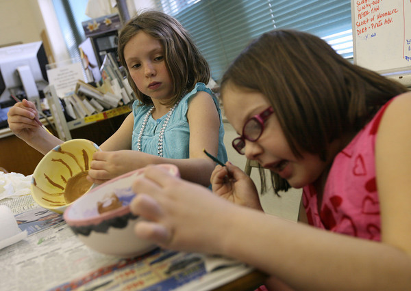 Essex: Maddie Lawler, left, and Faith Costello paint bowls at the TOHP Burnham Library that will be at the Open Door's Empty Bowl dinner in May. Photo by Kate Glass/Gloucester Daily Times