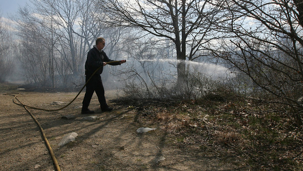 Gloucester: Gloucester Firefighter Mike Sonia battles a brush fire on Poles Hill yesterday afternoon. Photo by Kate Glass/Gloucester Daily Times