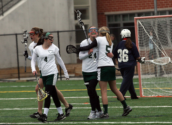 Manchester: Manchester Essex's Taylor Meek, right, hugs teammate Katie Cochard after she scored against Wilmington at Hyland Field yesterday afternoon. The Hornets won 16-9. Photo by Kate Glass/Gloucester Daily Times