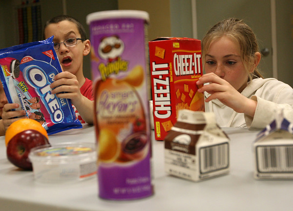 Domenic Romeo, left, and Isabella Ciluffo, both students at Beeman Memorial Elementary School, examine the nutrition lables on common snack foods during the Manchester Athletic Club's Enrichment Program yesterday. They were looking to see what types of fats were in the foods. Photo by Kate Glas/Gloucester Daily Times