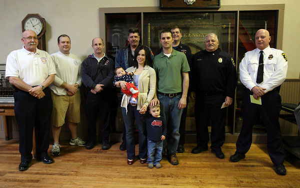 Gloucester: The Berthiaume family, Natalie, Jason, Luke, almost 2, and Maggie, 2 months, were reunited with the Gloucester rescue personnel who helped deliver Maggie at their Gloucester home on January 23rd. Pictured left to right are: Fire Chief Phil Dench, Firefighter/Paramedic Jon Sanger, Fire Capt. Bob Fuller, Firefighter Tom Savage, Firefighter/Paramedic Jeff Pool, Police Lt. Joe Aiello, and Police Chief Michael Lane. Not pictured is Patrolman Bill Cahill. The members of the police and fire departments were each presented with a stork pin for their role helping deliver the baby during a brief ceremony at Central Station yesterday. Photo by Kate Glass/Gloucester Daily Times
