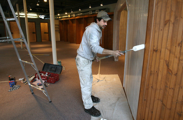 Bill Osterstuck of Sullivan & Son Painting applies primer to a wall in the former North Coast building in Manchester yesterday. J. Barrett & Co. Real Estate will be moving into the space. Photo by Kate Glass/Gloucester Daily Times