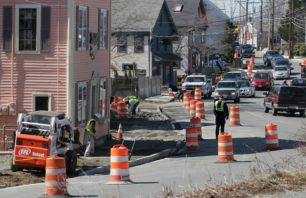 Essex: Crews work on repairing the sidewalk at the intersection of Main Street and Southern Avenue in Essex yesterday in front of Andrew Spindler Antiques and Essex Antiques. Many businesses have suffered while the sidewalk work is underway since it limits access to the stores. Photo by Kate Glass/Gloucester Daily Times