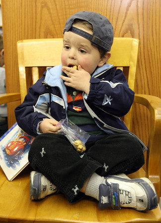 Essex: Elliot Davis, 3, snacks on caramel popcorn before reading a book at the TOHP Burnham Library. Photo by Kate Glass/Gloucester Daily Times