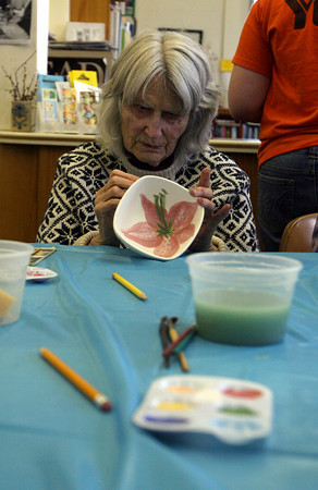 Essex: Bonnie Jean Malcolm paints a lily on a bowl for the Open Door's Empty Bowl Dinner during a painting event at the TOHP Burnham Library yesterday afternoon. Photo by Kate Glass/Gloucester Daily Times